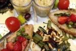 Antipasto conviviale_ crema di fave, spiedino greco, bruschetta di pane integrale con fragole e asparagi grigliati, pane carasao con catalogna piccante, pinoli e uvetta